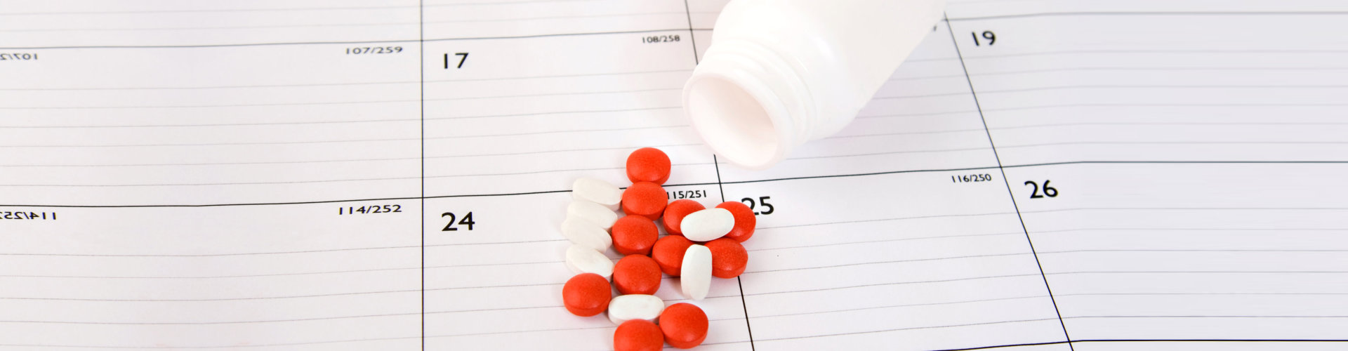 red and white pills placed on a calendar